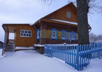 Бревенчатый жилой дом в тихой деревне, на берегу реки,